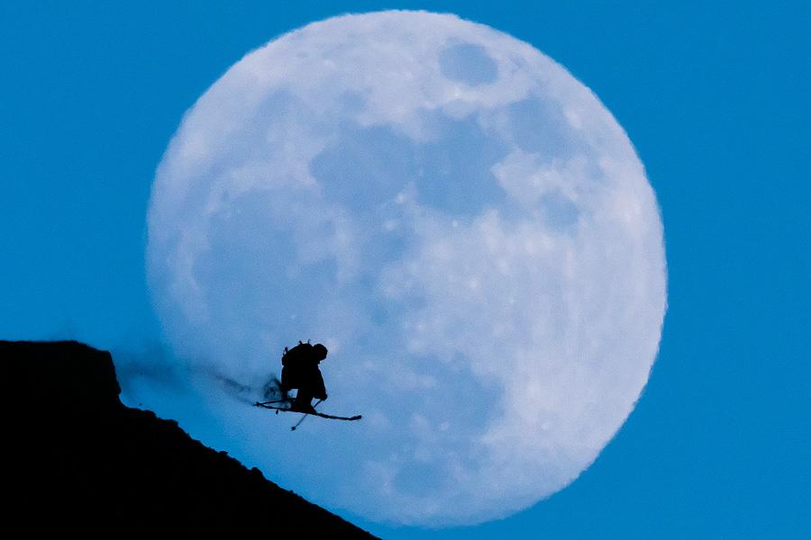 Eine Skifahrerin springt über einen Kicker vor dem aufgehenden Mond am 12. Februar 2014.