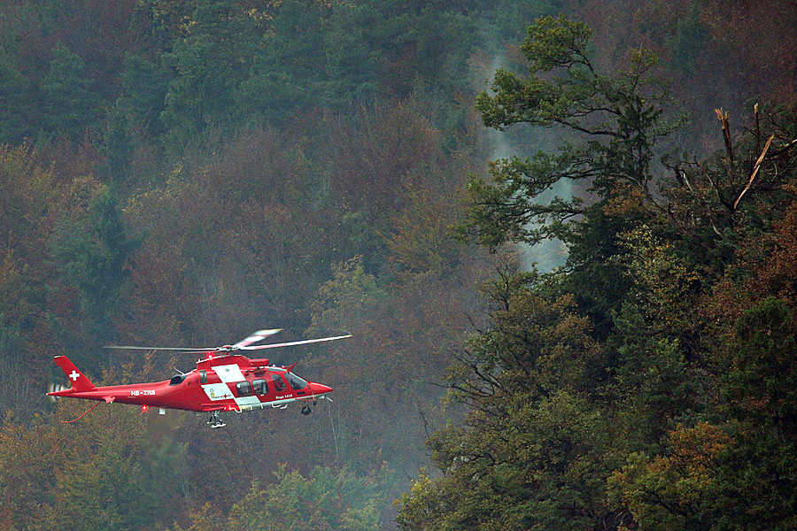 Ein Helikopter der REGA überfliegt das Absturzgebiet. Ein F/A-18 der Schweizer Luftwaffe stürzte bei schlechtem Wetter am Mittwoch, 23. Oktober 2013 bei Alpnachstad OW ab.