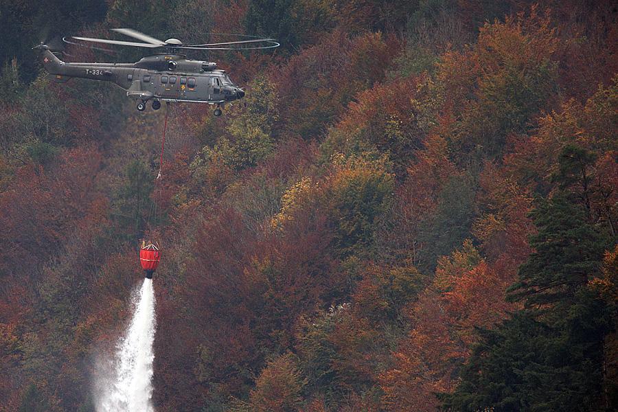 Ein Super Puma löscht das Feuer bei der Absturzstelle. Ein F/A-18 der Schweizer Luftwaffe stürzte bei schlechtem Wetter am Mittwoch, 23. Oktober 2013 bei Alpnachstad OW ab.