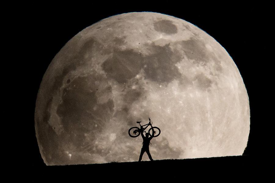Ein Mountainbiker posiert vor dem aufgehenden Vollmond am 25. April 2013.