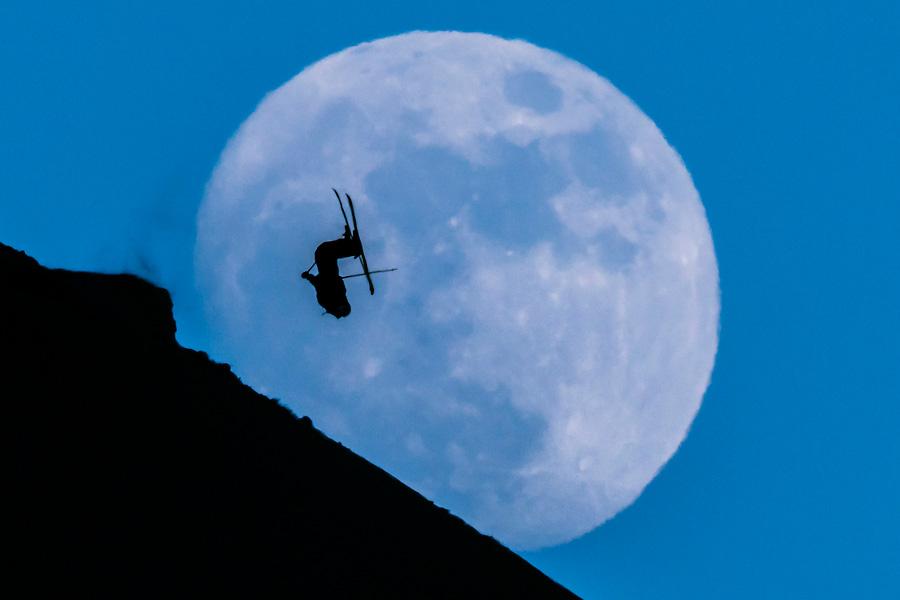 Ein Skifahrer springt über einen Kicker vor dem aufgehenden Mond am 12. Februar 2014.